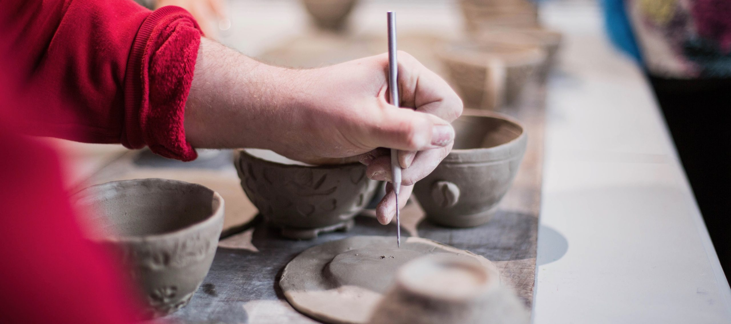 Close up of a clay artist working on making details in a clay plat with a clay knife.