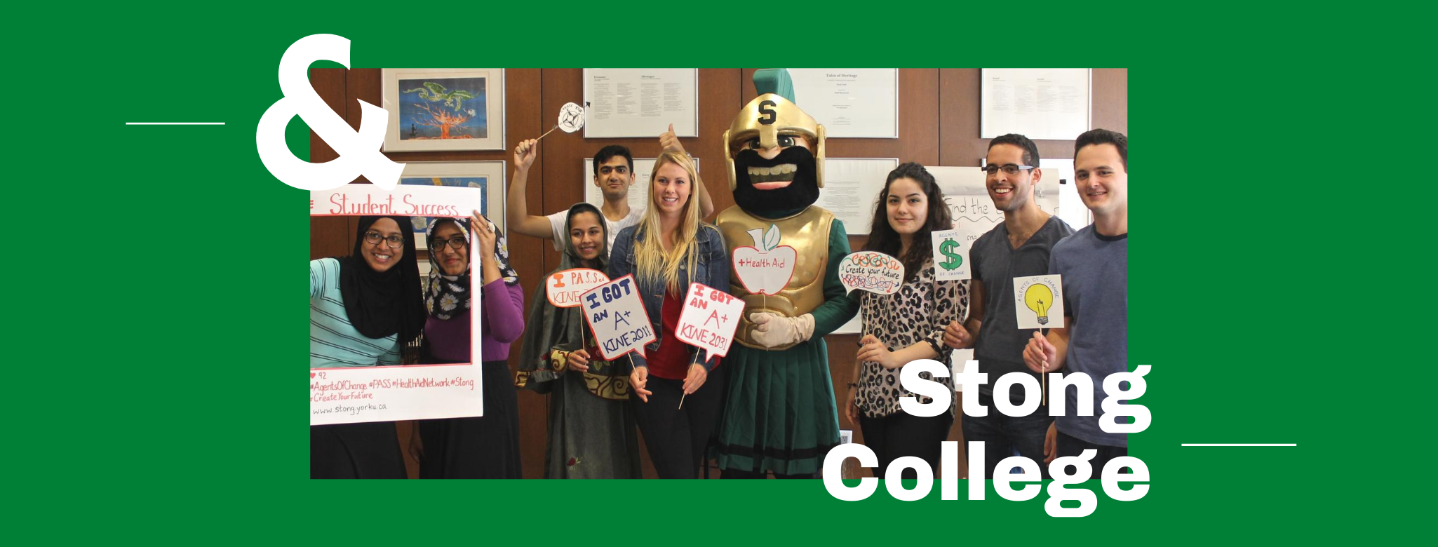 """9 students standing in line facing the camera. Students are holding """"Student Success"""" posters. In the center stands the Stong mascot."""